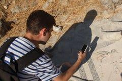 Turista che prende le immagini su un vecchio mosaico greco Immagini Stock Libere da Diritti