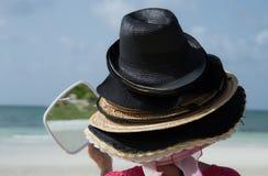 Turista che prova sui cappelli di Bahama. Fotografie Stock