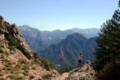 Turista che riposa e che guarda le montagne Immagini Stock Libere da Diritti