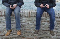 Turista che si siede sulla parete e che per mezzo di un telefono cellulare Immagini Stock