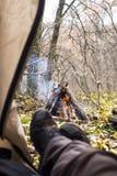 Turista che si trova in tenda e che esamina il fuoco nella foresta della montagna Immagini Stock