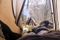 Turista che si trova in tenda e che esamina il fuoco nella foresta della montagna Fotografia Stock Libera da Diritti