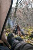 Turista che si trova in tenda e che esamina il fuoco nella foresta della montagna Fotografia Stock