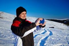 Turista che spara il paesaggio con il telefono cellulare Immagine Stock