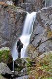 Turista che sta nella parte anteriore di una cascata Fotografia Stock Libera da Diritti