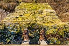 Turista che sta sull'alta parete di pietra, facente un'escursione il dettaglio delle scarpe Fotografie Stock
