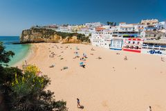 Turista che sunbatching alla spiaggia di Carvoeiro Immagini Stock
