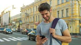 Turista che utilizza il suo telefono nel centro di una città Immagine Stock