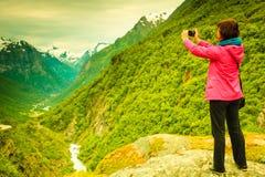 Turista com a câmera que toma a imagem nas montanhas Noruega Imagens de Stock Royalty Free