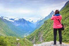 Turista com a câmera que toma a imagem nas montanhas Noruega Imagem de Stock