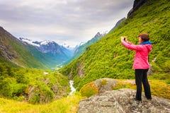 Turista com a câmera que toma a imagem nas montanhas Noruega Foto de Stock