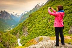 Turista com a câmera que toma a imagem nas montanhas Noruega Fotografia de Stock Royalty Free