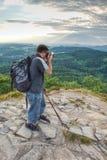 Turista com caminhada da trouxa em rochas da montanha imagens de stock