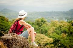 Turista com a trouxa que relaxa na rocha e que aprecia a admiração Fotos de Stock