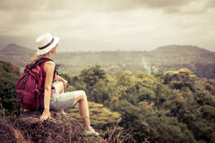 Turista com a trouxa que relaxa na rocha e que aprecia a admiração Imagem de Stock