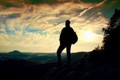 Turista con el soporte deportivo de la mochila en punto de visión rocoso y observación en bramido brumoso profundo del valle Alba foto de archivo