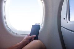 Turista con il biglietto e passaporto che si siede all'aereo della finestra Viaggio e concetto di viaggio fotografia stock