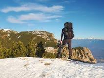 Turista con il grande zaino e le racchette da neve che stanno sul punto di vista roccioso e che guardano nelle montagne rocciose  Immagine Stock