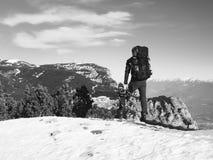 Turista con il grande zaino e le racchette da neve che stanno sul punto di vista roccioso e che guardano nelle montagne rocciose  Immagini Stock Libere da Diritti