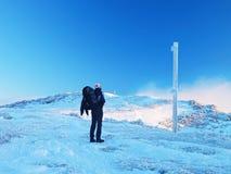 Turista con il grande zaino e le racchette da neve che stanno sul punto di vista roccioso e che guardano nelle montagne rocciose  Fotografie Stock Libere da Diritti