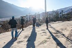 Turista con il supporto del cappotto sulla strada non asfaltata con luce solare con la montagna nel fondo Sul modo ad allo zero a Fotografia Stock