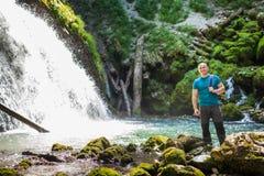 Turista con la cámara cerca de la cascada Foto de archivo