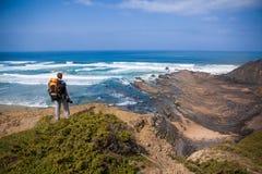 Turista con la mochila al borde de un acantilado hermoso cerca del océano Portugal Algarve Foto de archivo