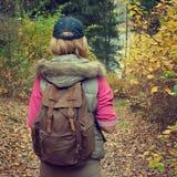 Turista con la mochila en bosque del otoño Imagen de archivo