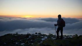 Turista con la mochila en la montaña rocosa en fondo del valle de niebla y del cielo azul en la salida del sol imagen de archivo libre de regalías