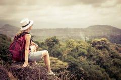 Turista con la mochila que se relaja en roca y que disfruta de la admiración Imagen de archivo