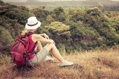 Turista con la mochila que se relaja en roca y que disfruta de la admiración Foto de archivo libre de regalías