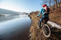 Turista con la mochila y la bicicleta que goza del río Imágenes de archivo libres de regalías