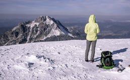 Turista con la mochila y polos que miran en las montañas del invierno fotos de archivo