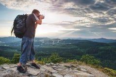 Turista con la passeggiata dello zaino sulle rocce della montagna immagine stock
