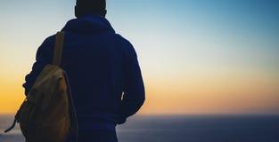 Turista con lo sguardo dello zaino del tramonto stupefacente di vista sul mare sul mare blu del fondo, tipo della viandante dei p immagini stock libere da diritti