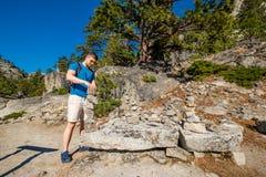 Turista con lo zaino che fa un'escursione in montagne Fotografia Stock