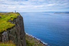 Turista con lo zaino che sta sulla testa della fiera della scogliera, Irlanda del Nord, Regno Unito Fotografie Stock