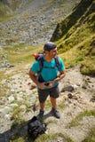 Turista con lo zaino sulla montagna Fotografie Stock Libere da Diritti