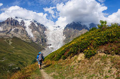 Turista con una mochila abajo del glaciar de desatención de la montaña Fotos de archivo libres de regalías