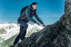 Turista con una mochila que se arrastra en rocas al top en el fondo de montañas Logro de la motivación y de la meta foto de archivo libre de regalías