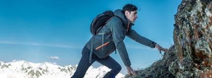 Turista con una mochila que se arrastra en rocas al top en el fondo de montañas Logro de la motivación y de la meta imagen de archivo libre de regalías