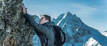 Turista con una mochila que se arrastra en rocas al top en el fondo de montañas Logro de la motivación y de la meta fotografía de archivo libre de regalías