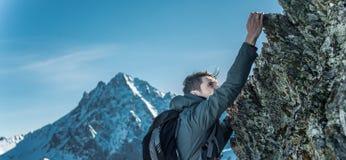 Turista con una mochila que se arrastra en rocas al top en el fondo de montañas Logro de la motivación y de la meta fotos de archivo libres de regalías