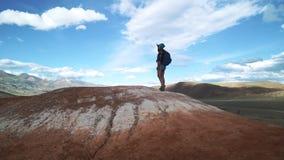 Turista con uno zaino che sta sul picco di montagna che esamina i fps di distanza 50 stock footage