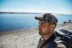 Turista considerável do homem com a trouxa que olha ao rio bonito no dia de verão quente imagem de stock