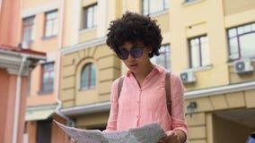 Turista consideravelmente fêmea que olha o mapa, procurando por lugares sightseeing da cidade, curso video estoque