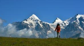 Turista contro il fondo nevoso delle cime Fotografia Stock