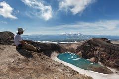 Turista in cratere del vulcano attivo di Gorely che guarda nel bello lago del cratere La Russia, Kamchatka Fotografie Stock
