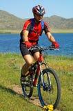 Turista da bicicleta ao lado do lago Foto de Stock Royalty Free