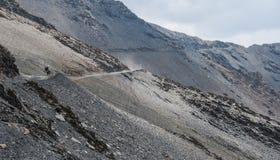 Turista da bicicleta na estrada da montanha Fotografia de Stock